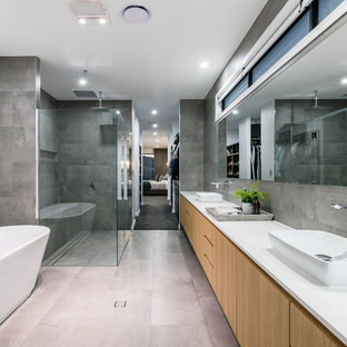 Photo of an expansive contemporary master bathroom in Brisbane with light wood cabinets, a double shower, gray tile, grey walls, porcelain floors, a vessel sink, engineered quartz benchtops, grey floor, a hinged shower door, white benchtops, flat-panel cabinets and a freestanding tub.
