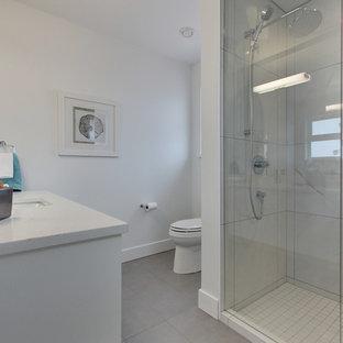 Ispirazione per una grande stanza da bagno moderna con ante lisce, ante bianche, doccia alcova, WC monopezzo, piastrelle bianche, lastra di pietra, pareti bianche, pavimento in laminato, lavabo integrato, top in marmo, pavimento grigio, porta doccia scorrevole e top bianco