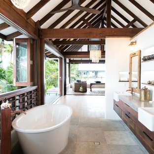 Tropical master bathroom in Cairns with flat-panel cabinets, medium wood cabinets, a freestanding tub, white walls, a drop-in sink, concrete benchtops, grey floor and grey benchtops.