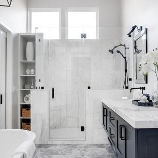 ロサンゼルスの中サイズのビーチスタイルのおしゃれなマスターバスルーム (シェーカースタイル扉のキャビネット、置き型浴槽、アルコーブ型シャワー、白いタイル、白い壁、グレーの床、開き戸のシャワー、白い洗面カウンター、青いキャビネット、分離型トイレ、大理石タイル、大理石の床、アンダーカウンター洗面器、クオーツストーンの洗面台) の写真