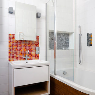 This is an example of a small contemporary family bathroom in London with flat-panel cabinets, white cabinets, a built-in bath, a shower/bath combination, a one-piece toilet, white tiles, grey walls, ceramic flooring, an integrated sink and multi-coloured floors.