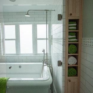 Foto de cuarto de baño de estilo americano, de tamaño medio, con armarios estilo shaker, puertas de armario de madera clara, bañera exenta, combinación de ducha y bañera, baldosas y/o azulejos blancos, baldosas y/o azulejos de mármol y ducha con puerta con bisagras