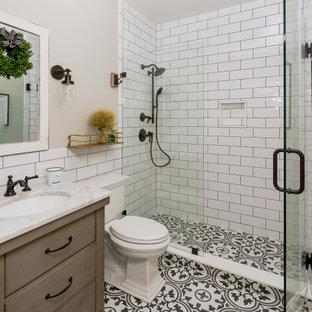 Immagine di una piccola stanza da bagno country con pareti grigie, consolle stile comò, ante marroni, piastrelle bianche, piastrelle in gres porcellanato, pavimento in cementine, lavabo a consolle, top in marmo, pavimento multicolore, porta doccia a battente e top bianco