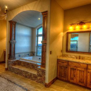 他の地域の大きいラスティックスタイルのおしゃれなマスターバスルーム (レイズドパネル扉のキャビネット、中間色木目調キャビネット、ベージュのタイル、茶色いタイル、マルチカラーのタイル、ボーダータイル、茶色い壁、磁器タイルの床、アンダーカウンター洗面器、御影石の洗面台、大型浴槽) の写真