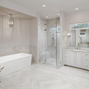 Klassisches Badezimmer En Suite mit profilierten Schrankfronten, beigen Schränken, freistehender Badewanne, Duschnische, beigefarbenen Fliesen, beiger Wandfarbe, Unterbauwaschbecken und Falttür-Duschabtrennung in Houston