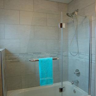 Ejemplo de cuarto de baño clásico renovado, pequeño, con lavabo bajoencimera, armarios tipo mueble, puertas de armario de madera en tonos medios, encimera de cuarzo compacto, bañera empotrada, combinación de ducha y bañera, sanitario de dos piezas, baldosas y/o azulejos grises, baldosas y/o azulejos de vidrio, paredes grises y suelo de baldosas de porcelana