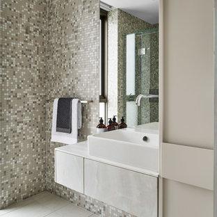 Ejemplo de cuarto de baño contemporáneo, pequeño, con armarios con paneles lisos, puertas de armario grises, ducha doble, sanitario de pared, baldosas y/o azulejos multicolor, baldosas y/o azulejos de cerámica, paredes blancas, suelo de baldosas de porcelana, lavabo tipo consola, encimera de ónix, suelo beige, ducha con puerta con bisagras y encimeras grises