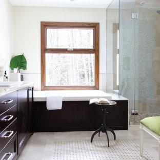 Immagine di una stanza da bagno design con lavabo a colonna, ante lisce, ante in legno bruno, top alla veneziana, vasca da incasso, doccia a filo pavimento, piastrelle bianche, piastrelle in gres porcellanato, pareti beige e parquet chiaro