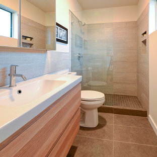 Photo of a small midcentury bathroom in Austin with an integrated sink, an alcove shower, a two-piece toilet, flat-panel cabinets, medium wood cabinets, gray tile, ceramic tile, white walls and ceramic floors.