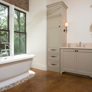 Example of a mid-sized classic master beige tile concrete floor freestanding bathtub design in Charleston with an undermount sink, recessed-panel cabinets, gray cabinets, granite countertops and white walls
