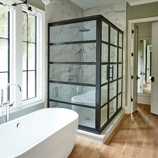 Inspiration for a transitional master bathroom in Charlotte with a freestanding tub, multi-coloured tile, stone slab, grey walls and light hardwood floors.