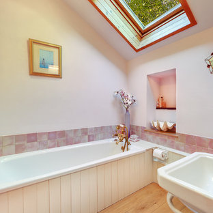 Inspiration for a farmhouse bathroom in Devon with white cabinets, light hardwood flooring, an alcove bath and pink tiles.