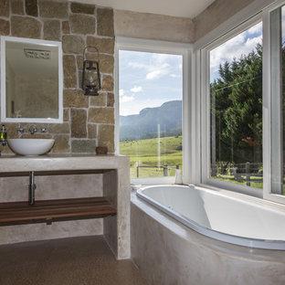 Foto de cuarto de baño principal, campestre, de tamaño medio, con armarios abiertos, baldosas y/o azulejos de piedra, bañera encastrada, sanitario de una pieza, suelo de cemento, lavabo sobreencimera y ducha abierta