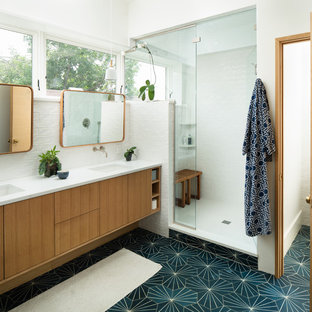 This is an example of a midcentury master bathroom in Denver with flat-panel cabinets, light wood cabinets, an alcove shower, white tile, subway tile, white walls, an undermount sink, green floor, a hinged shower door and white benchtops.