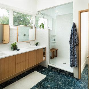 Retro Badezimmer En Suite mit flächenbündigen Schrankfronten, hellen Holzschränken, Duschnische, weißen Fliesen, Metrofliesen, weißer Wandfarbe, Unterbauwaschbecken, grünem Boden, Falttür-Duschabtrennung und weißer Waschtischplatte in Denver