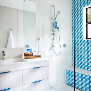 This is an example of a medium sized contemporary family bathroom in Austin with blue tiles, multi-coloured tiles, white tiles, cement tiles, flat-panel cabinets, white cabinets, a built-in shower, an integrated sink, white walls, solid surface worktops and an open shower.