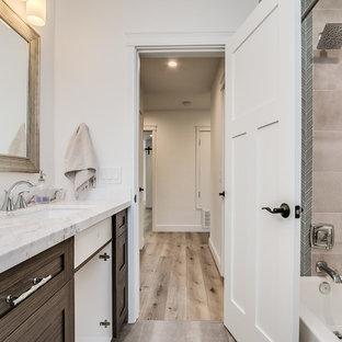 Imagen de cuarto de baño de estilo de casa de campo, de tamaño medio, con armarios con paneles empotrados, puertas de armario marrones, combinación de ducha y bañera, baldosas y/o azulejos de cerámica, suelo vinílico, lavabo bajoencimera, encimera de granito, ducha con cortina y encimeras blancas