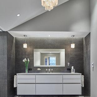 Modernes Badezimmer En Suite mit flächenbündigen Schrankfronten, weißen Schränken, grauen Fliesen, grauer Wandfarbe und grauem Boden in Washington, D.C.