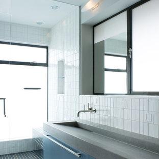 Imagen de cuarto de baño moderno con lavabo de seno grande, armarios con paneles lisos, puertas de armario azules y baldosas y/o azulejos blancos