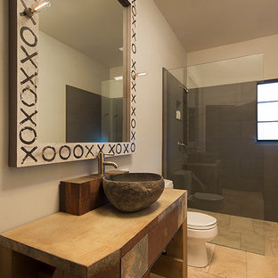 Bathroom - mid-sized farmhouse 3/4 beige tile and stone tile limestone floor bathroom idea in San Francisco with a two-piece toilet, beige walls, a vessel sink and wood countertops