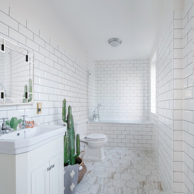 Large trendy 3/4 white tile and subway tile beige floor bathroom photo in London with recessed-panel cabinets, white cabinets, a one-piece toilet, white walls and a console sink