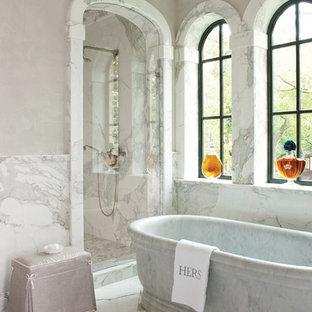 Foto di una stanza da bagno mediterranea con vasca freestanding, doccia alcova, piastrelle bianche, piastrelle di marmo, pareti grigie, pavimento bianco e porta doccia a battente