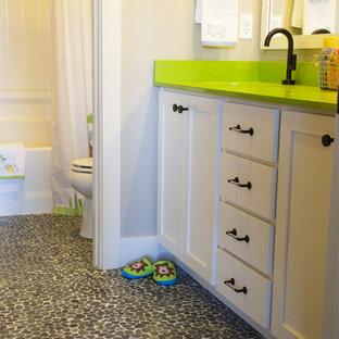 Foto di una stanza da bagno per bambini tradizionale con lavabo sottopiano, ante in stile shaker, ante bianche, top in quarzo composito, vasca da incasso, vasca/doccia, WC a due pezzi, piastrelle nere, piastrelle di ciottoli e pareti grigie