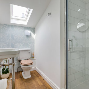 Design ideas for a small transitional 3/4 bathroom in London with an alcove shower, a two-piece toilet, blue tile, white tile, ceramic tile, white walls, medium hardwood floors, a console sink and a hinged shower door.