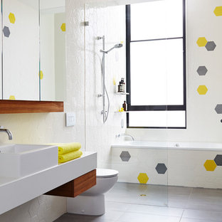 This is an example of a medium sized scandi family bathroom in Melbourne with a vessel sink, white walls, a built-in bath, ceramic tiles, porcelain flooring, engineered stone worktops, a built-in shower, a one-piece toilet and multi-coloured tiles.