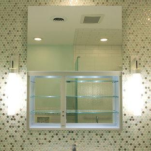 Modelo de cuarto de baño infantil, actual, de tamaño medio, con lavabo sobreencimera, encimera de vidrio reciclado, bañera encastrada sin remate, ducha empotrada, sanitario de pared y baldosas y/o azulejos multicolor