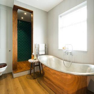 Inredning av ett lantligt badrum, med ett fristående badkar, en hörndusch, en vägghängd toalettstol, vita väggar, mellanmörkt trägolv, grön kakel och tunnelbanekakel