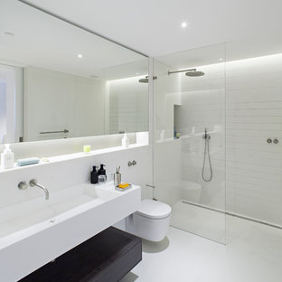 Example of a mid-sized trendy white tile walk-in shower design in London with a trough sink, a wall-mount toilet and white walls