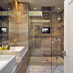 Trendy master brown tile and travertine tile travertine floor walk-in shower photo in London with a vessel sink, flat-panel cabinets and medium tone wood cabinets