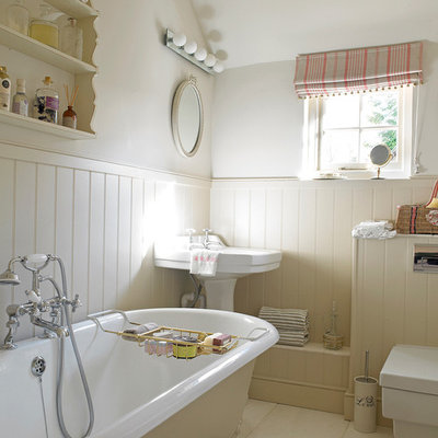 Inspiration for a shabby-chic style claw-foot bathtub remodel in Wiltshire with a wall-mount toilet, beige walls and a pedestal sink