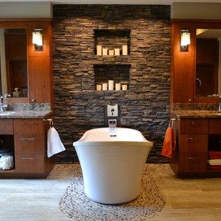 Ispirazione per una stanza da bagno contemporanea con ante lisce, ante in legno bruno, vasca freestanding e pavimento con piastrelle di ciottoli