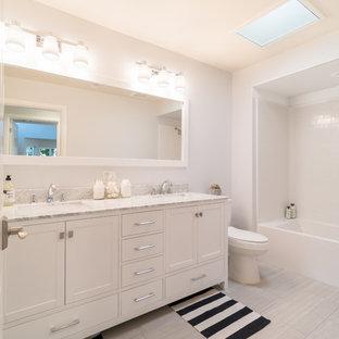 他の地域のビーチスタイルのおしゃれな浴室 (落し込みパネル扉のキャビネット、白いキャビネット、コーナー型浴槽、白い壁、一体型シンク、グレーの床) の写真
