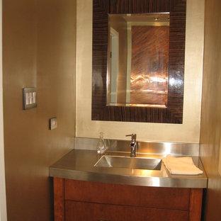 Ispirazione per una piccola stanza da bagno con doccia tradizionale con ante lisce, ante in legno scuro, pareti beige, lavabo integrato e top in acciaio inossidabile