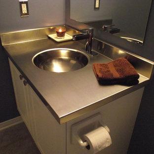 Immagine di una piccola stanza da bagno con doccia minimal con ante con bugna sagomata, ante bianche, pareti blu, pavimento in travertino, lavabo integrato e top in acciaio inossidabile