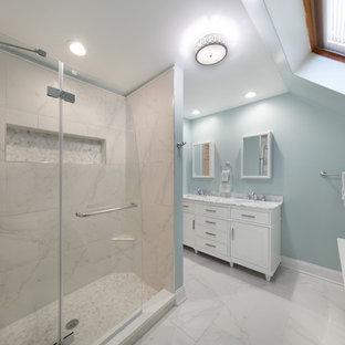 Ispirazione per una stanza da bagno padronale moderna di medie dimensioni con ante con bugna sagomata, ante bianche, vasca freestanding, doccia ad angolo, WC monopezzo, piastrelle bianche, lastra di pietra, pareti blu, pavimento in marmo, lavabo sottopiano e top in marmo
