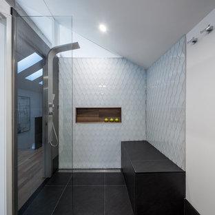 Diseño de cuarto de baño principal, actual, de tamaño medio, con ducha esquinera, baldosas y/o azulejos grises, baldosas y/o azulejos blancos, baldosas y/o azulejos de vidrio, paredes blancas, armarios abiertos, puertas de armario de madera clara, suelo de pizarra, lavabo de seno grande y encimera de madera