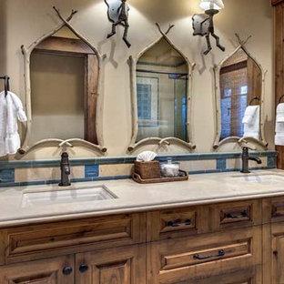 サクラメントの大きいカントリー風おしゃれなマスターバスルーム (レイズドパネル扉のキャビネット、中間色木目調キャビネット、コーナー設置型シャワー、分離型トイレ、青いタイル、セラミックタイル、ベージュの壁、玉石タイル、アンダーカウンター洗面器、珪岩の洗面台、ベージュの床、開き戸のシャワー) の写真