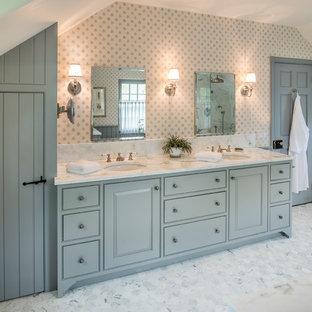 Cette image montre une grand salle de bain principale traditionnelle avec un placard à porte affleurante, des portes de placard bleues, un sol en marbre, un lavabo encastré, un plan de toilette en marbre, un mur multicolore et un sol gris.