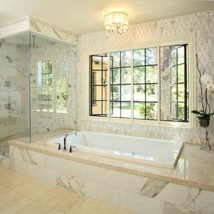 Réalisation d'une salle de bain principale tradition de taille moyenne avec un bain bouillonnant, une douche d'angle, un carrelage gris, un carrelage de pierre, un mur gris, un sol en carrelage de porcelaine et un sol beige.