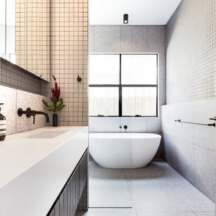 Inspiration for a mid-sized contemporary master bathroom in Melbourne with a freestanding tub, gray tile, porcelain tile, engineered quartz benchtops, white benchtops, flat-panel cabinets, dark wood cabinets, a curbless shower, grey walls, an undermount sink, grey floor and an open shower.