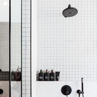 Immagine di una stanza da bagno padronale minimal di medie dimensioni con ante nere, vasca freestanding, doccia aperta, WC sospeso, piastrelle grigie, piastrelle a mosaico, pareti grigie, pavimento alla veneziana, lavabo sottopiano, top in quarzo composito, pavimento grigio, doccia aperta e top bianco
