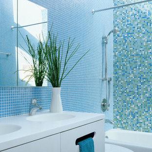 Ejemplo de cuarto de baño actual, pequeño, con baldosas y/o azulejos en mosaico, armarios con paneles lisos, puertas de armario blancas, bañera empotrada, combinación de ducha y bañera, sanitario de dos piezas, baldosas y/o azulejos azules, paredes azules, lavabo integrado, encimera de acrílico y suelo con mosaicos de baldosas