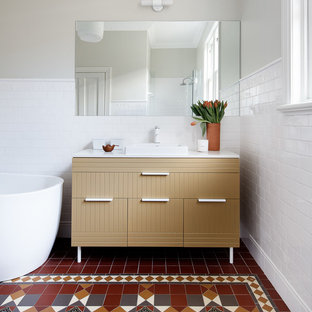 Inspiration for an eclectic bathroom in Sydney with furniture-like cabinets, a freestanding tub, white tile, ceramic tile, cement tiles, a drop-in sink, engineered quartz benchtops, multi-coloured floor, white benchtops, beige cabinets and beige walls.