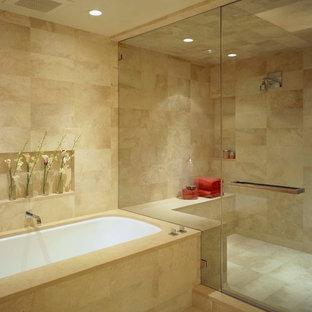 Esempio di una stanza da bagno design con vasca sottopiano, doccia alcova, piastrelle beige, porta doccia a battente e piastrelle in travertino