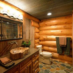 Diseño de cuarto de baño rural con lavabo sobreencimera, puertas de armario de madera oscura, bañera empotrada y combinación de ducha y bañera