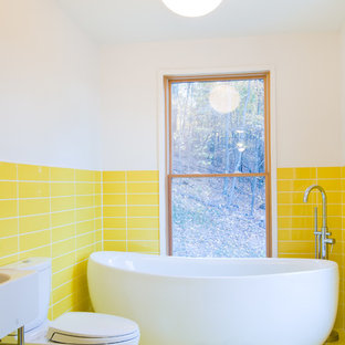 На фото: маленькая детская ванная комната в современном стиле с монолитной раковиной, отдельно стоящей ванной, раздельным унитазом, желтой плиткой, керамогранитной плиткой, белыми стенами, полом из керамогранита и желтым полом с